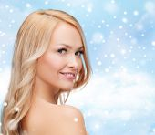 heath, people and beauty concept - beautiful young woman with bare shoulders over blue sky, snow and clouds background