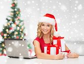 technology, holidays, online shopping and people concept - woman in santa helper hat with gift boxes and laptop computer over living room background