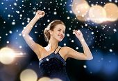 people, party, holidays and glamour concept - smiling woman dancing with raised hands over night lights background