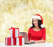 christmas, holidays, technology and people concept - smiling woman in santa helper hat with gift boxes and laptop computer over yellow lights background