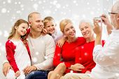 family, holidays, generation, christmas and people concept - smiling family with camera photographing and sitting on couch at home