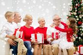 family, holidays, generation, christmas and people concept - smiling family with gift boxes sitting on couch and hugging at home