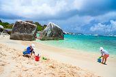Kids wearing sun protection rash guard playing at beach during summer vacation