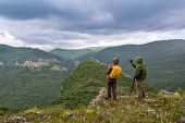 Tourists With A Camera In The Mountains