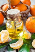 Bottle Of Essential Citrus Oil And Ripe Tangerines In Basket On Old Kitchen Table.