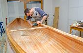 foto of canoe boat man  - Young carpenter sanding new canoe in workshop - JPG