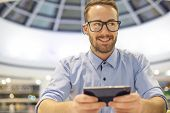 Smiling Businessman with electronic device on hand, blurred background of indor shopping mall