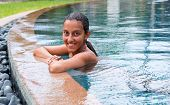 Pretty Smiling Young Asian Indian Beauty Resting on the Side of the Pool after Swimming while Looking at the Camera.