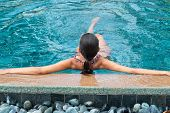 Rear view of long hair woman leaning at the edge of beautiful pool with wide open arms.