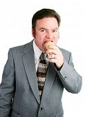 Handsome man in business suit eating a chocolate ice cream waffle cone.  Isolated on white.