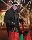 A senior man happily carrying filled shopping bags outside from a Christmas decorated mall.