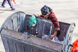 stock photo of dumpster  - Homeless woman is searching for food in garbage dumpster - JPG