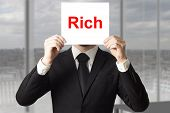 stock photo of employee month  - businessman in black suit hiding face behind sign rich - JPG