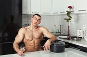 stock photo of pinafore  - Naked man resting in the kitchen with his hand on the pan - JPG