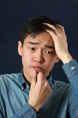 image of disappointed  - Disappointed young Asian man looking sideways - JPG