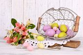 foto of easter basket eggs  - Easter composition with Easter eggs in basket and flowers - JPG