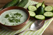 stock photo of cucumber  - Cucumber soup in bowl on rustic wooden table background - JPG