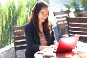 foto of handphone  - A portrait of a Young businesswoman work oudoor in a cafe - JPG