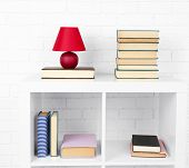 stock photo of book-shelf  - Wooden shelf with books and lamp on brick wall background - JPG