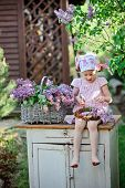 picture of dress-making  - adorable child girl in pink plaid dress making lilac flower wreath in spring garden - JPG