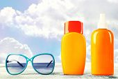 stock photo of suntanning  - Bottles with suntan cream with sunglasses on table isolated on white - JPG