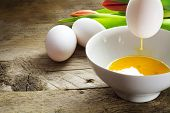 stock photo of yolk  - blow out eggs for Easter decoration egg with rinning yolk over a bowl more white eggs and tulips in the background on old wood copy space - JPG