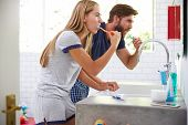 stock photo of pajamas  - Couple In Pajamas Brushing Teeth In Bathroom - JPG