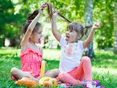 foto of tease  - Girls kids sisters friends teasing showing off tongues sitting on grass - JPG