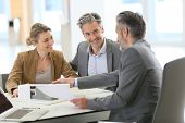 stock photo of maturity  - Mature couple meeting architect for construction project - JPG