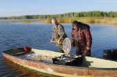 pic of fishermen  - fishermen unloading fish from boat in containers - JPG