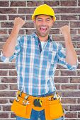 image of clenched fist  - Excited manual worker clenching fists against red brick wall - JPG