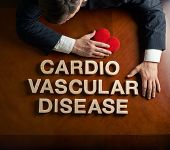 image of cardio  - Phrase Cardio Vascular Disease made of wooden block letters and devastated middle aged caucasian man in a black suit sitting at the table with the red symbolic heart - JPG