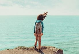 pic of flutter  - Traveler young woman with backpack standing on coastline near the sea in windy weather her hair fluttering in the wind - JPG
