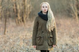 picture of dreadlock  - Young beautiful blonde hipster woman in scarf and parka with dreadlocks hairstyle posing on a blurry forest background - JPG