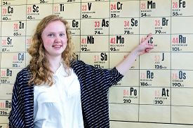 image of periodic table elements  - Caucasian teenage girl pointing finger at periodic table - JPG