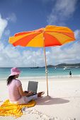 stock photo of tropical island  - a woman working on the beach in whitsunday island - JPG