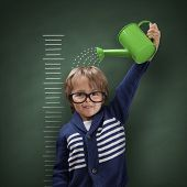 stock photo of measuring height  - Young boy trying to make himself taller with watering can measuring his growth in height against a blackboard scale - JPG