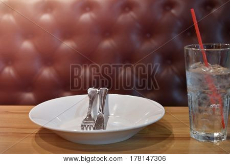 White plate fork and knife all placed on the table. Nearby there is a glass of water and a straw.