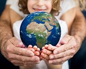 Family Holding Earth Planet In Hands poster