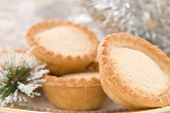 Traditional Christmas mince pies with silver tinsel and ornament background