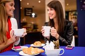Women having coffee and snacks at a coffee shop in shopping mall poster