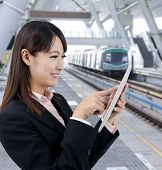 Young business woman using touch pad in the train station