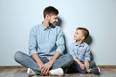 Father and his son sitting on floor near color wall poster
