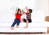 Two african american kids playing with pillows