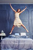 Low angle of an attractive young woman jumping energetically on the bed. Extremely excited woman in  poster