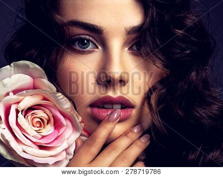 poster of Beautiful face of a young woman with a smoky eye makeup  and rose flower. Sexy  brown-haired woman w
