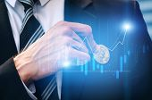 Close Up Hand Of Investor Business Man Pick Bitcoin From Suit Pocket With Graphic Candle Stick Graph poster