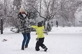 Mom And Son Playing Snowball Fight And Smiling In Winter.  Happy Family (mother And Son) Having Fun  poster