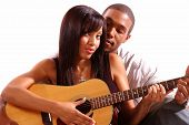 African American man teaching his girlfrind how to play guitar