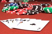 One of the highest hands in poker a Clubs Royal Flush on a red felt gaming table with a poker jackpo